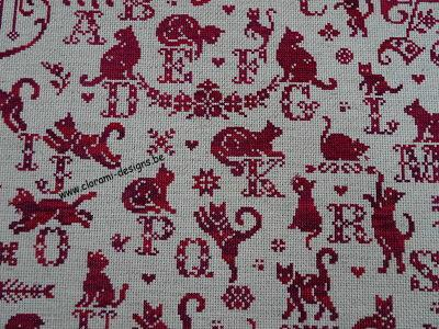 red cross stitch sampler with cross stitch letters and cats