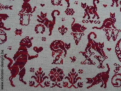 red crossstitch sampler with ancient crossstitch letters and cats