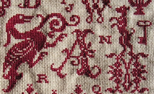 detail red cross stitch sampler